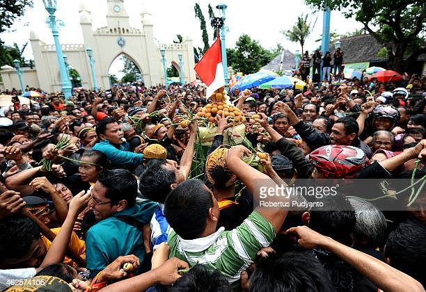 Indonesian people reach for the Gunungan offering during Grebeg Maulud at Surakarta Mosque on January 14 2014 in Solo City Indonesia Indonesia...