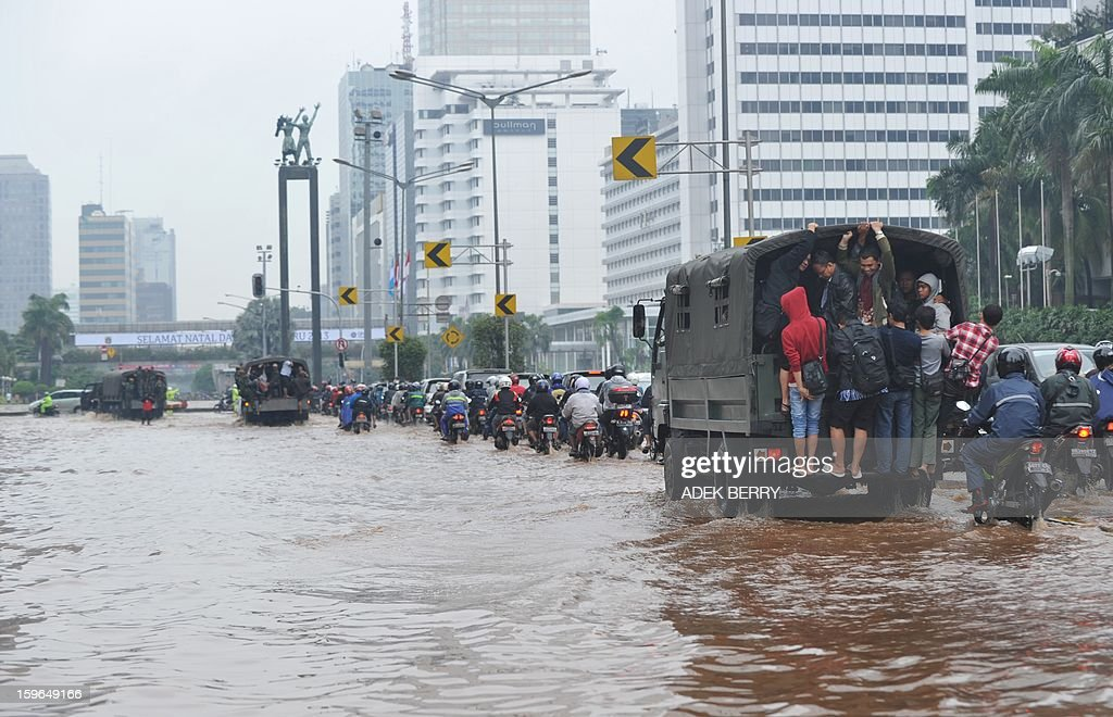 Indonesian people ride military trucks to reach their offices on a flooded main street in Jakarta on February 18, 2013. Floods which have made more than 19,000 people homeless and killed three brought parts of the Indonesian capital to a standstill on January 17, with even the president forced to roll up his trousers.