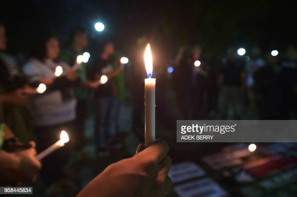 Indonesian people take part in a candlelight vigil in support of the victims and their relatives following a series of bomb attacks in Surabaya, in...