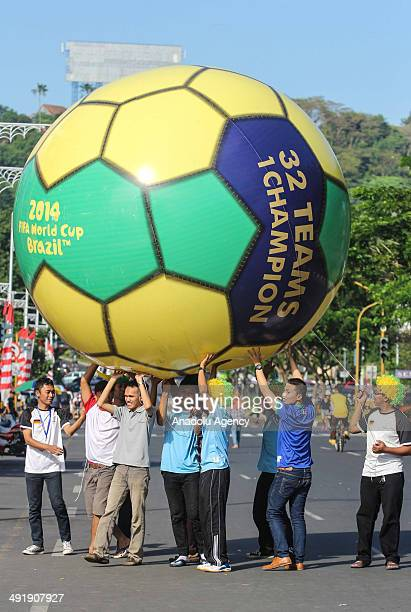Indonesian peoples lifting a giant ball to welcome the 2014 FIFA World Cup International men's football tournament scheduled to take place in Brazil...
