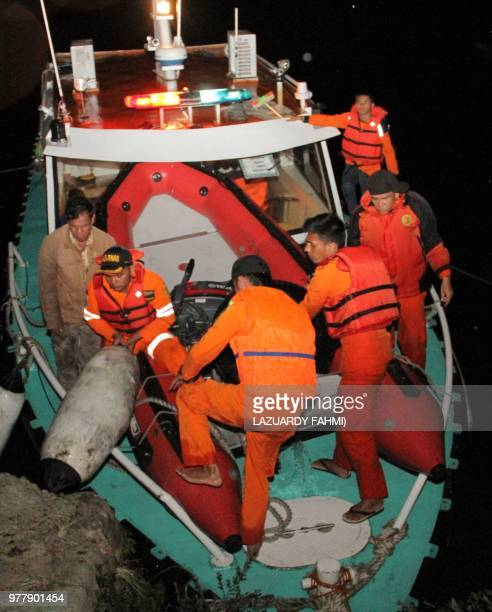 Indonesian personnel disembark from a rescue boat as it returns to harbour due to bad weather after a boat overturned in Lake Toba in the province of...