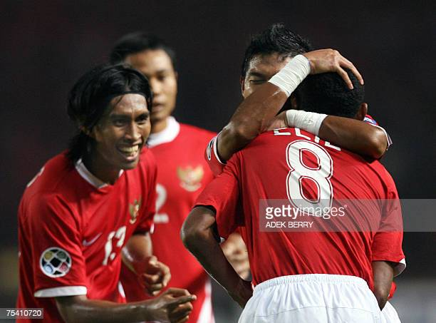 Indonesian player Bambang Pamungkas hugs Elie Aiboy as Budi Sudarsono smiles to celebrate a score for Indonesia during their Asian Cup 2007 Group D...