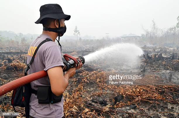 Indonesian police and firemen work to put out fire in Rimbo Panjang the Sumatran city of Pekanbaru on September 16 2015 in Riau Indonesia Indonesia...