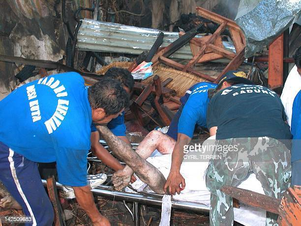 Indonesian police and rescuer workers remove victims at the site of a bomb blast in the tourist area of Kuta Bali 13 October 2002 At least 150 people...