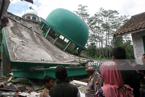 Indonesian police and residents visit a collapsed mosque after an earthquake in Kranggan village in Banyumas Central Java on January 25 2014 The...