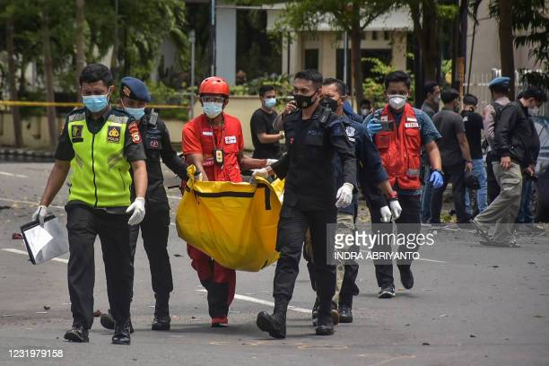 Indonesian police carry a bag with the remains of a suspected suicide bomber after an explosion outside a church in Makassar on March 28, 2021.