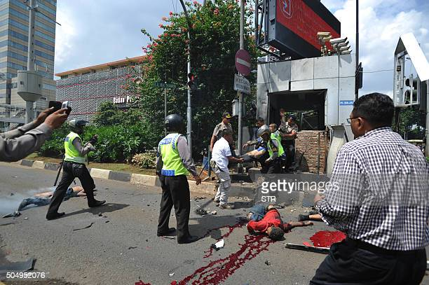 Indonesian police carry a wounded policeman near dead bodies on the road outside the bombdamaged traffic police outpost outside a damaged Starbucks...