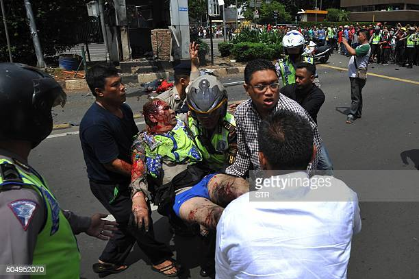 Indonesian police carry a wounded policeman past dead bodies on the road outside the bombdamaged traffic police outpost outside a damaged Starbucks...