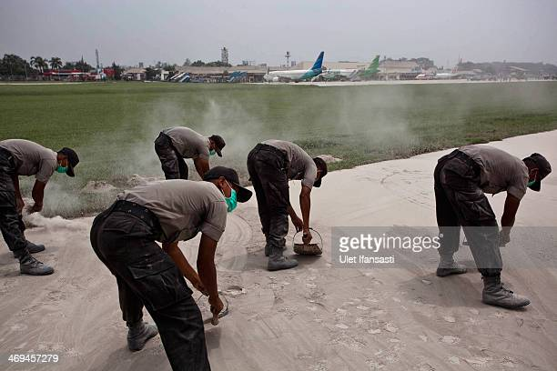 Indonesian police clean the runway of the international airport Adisucipto as covered by ash from the eruptions of the Mount Kelud on February 15...