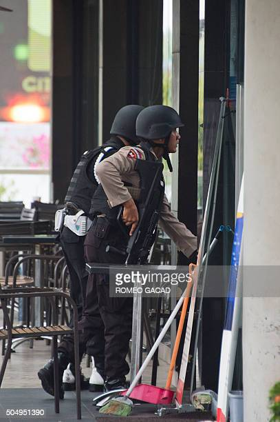 Indonesian police commandos secure the area outside a damaged Starbucks coffee shop after a series of explosions hit central Jakarta on January 14...