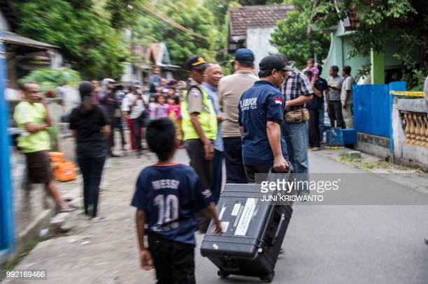 Indonesian police conduct an investigation at a house in the city of Bangil East Java province on July 5 after an alleged terrorist who managed to...