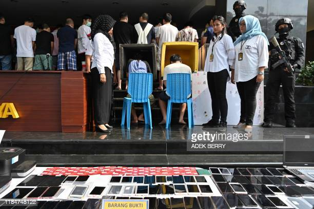 Indonesian police display evidence and Chinese and Indonesian suspects during a press conference in Jakarta on November 26, 2019. - Dozens of Chinese...