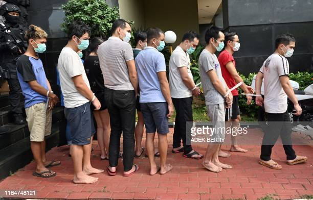 Indonesian police escort a group of Chinese and Indonesian suspects after a press conference in Jakarta on November 26, 2019. - Dozens of Chinese...