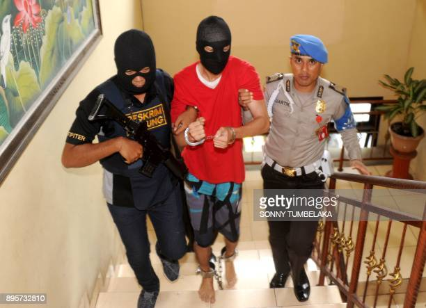 Indonesian police escort US prisoner Christian Beasley to a press conference at a police station in Badung regency on Indonesia's resort island of...