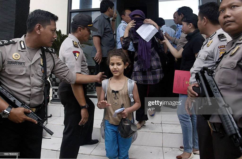Indonesian police guard illegal immigrants from Iraq and Iran at Surabaya police station in East Java on March 15, 2013. 80 immigrants from Iran and Iraq were arrested in Tuban as they were traveling on a bus and in an SUV. Indonesia is used as a transit hub, where potential immigrants pay people-smugglers for passage on leaky wooden vessels after fleeing their home countries. AFP PHOTO / Juni KRISWANTO