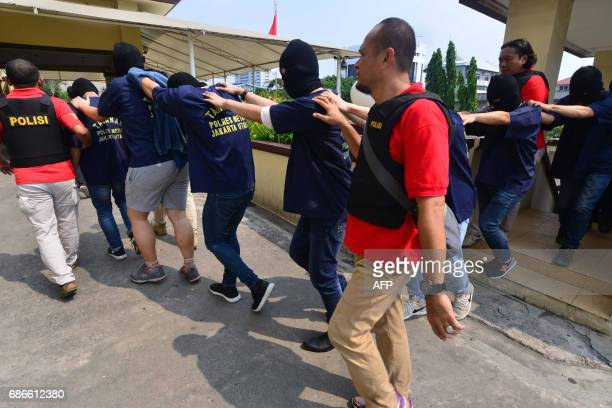 Indonesian police guard men arrested in a recent raid during a press conference at a police station in Jakarta on May 22 2017 Indonesian police have...