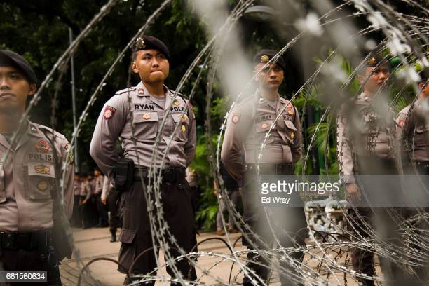 Indonesian Police guard the road leading to the Presidential Palace ahead of a protest against the Jakarta governor Basuki Tjahaja Purnama known...