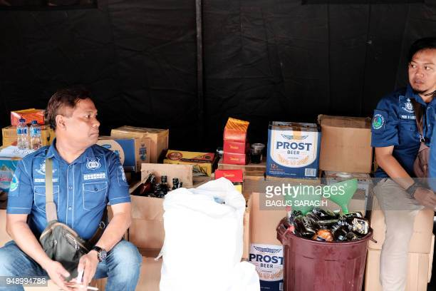 Indonesian police guard the stock of recently seized bootleg liquor prior to a press conference in Jakarta. - Police have arrested the main suspect...