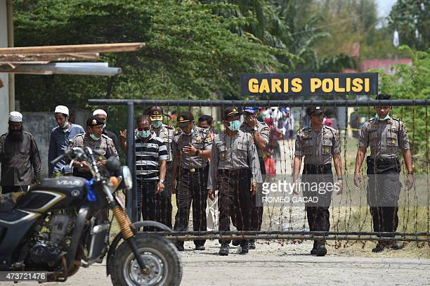 Indonesian police inspect the migrant confinement area in the fishing port of Kuala Langsa in Aceh province on May 17 2015 where hundreds of migrants...