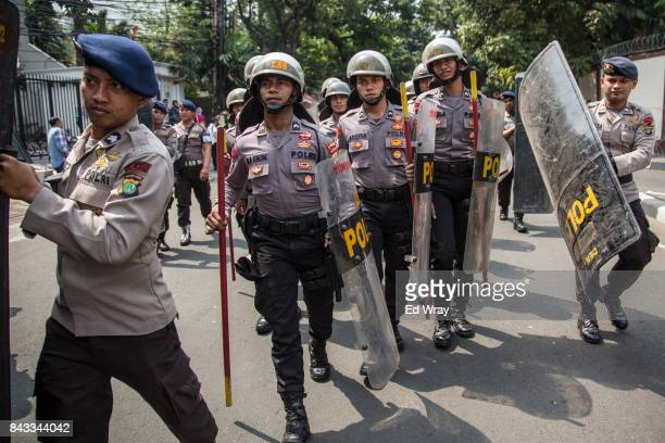 Indonesian police move into position to protect the Myanmar Embassy during a demonstration by thousands of Indonesian Muslims in support of Myanmar's...