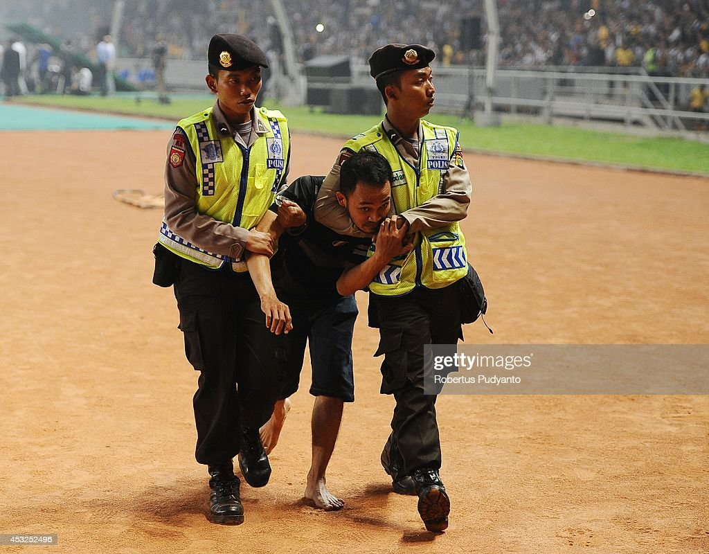 Indonesian Police officers arrest a Juventus FC supporter who invaded the pitch during the pre season friendly match between Indonesia Selection All Star Team and Juventus FC at Gelora Bung Karno Stadium on August 6, 2014 in Jakarta, Indonesia. Juventus FC win the game 8-1.