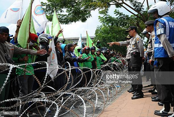 Indonesian Police officers block the protesters with barbed wire barricades during a protest demanding higher wages on October 31 2013 in Surabaya...