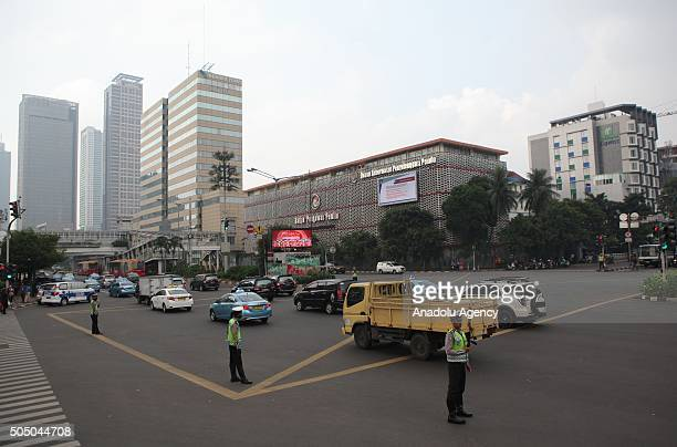 Indonesian police officers regulate traffic flow in front of the damaged Starbucks Coffe building in Jakarta on January 15 a day after a series of...
