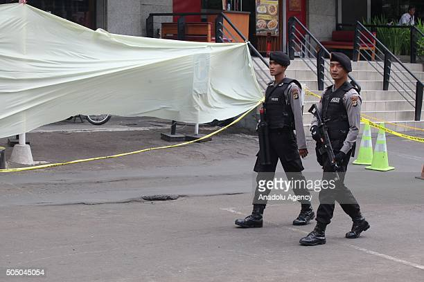 Indonesian police officers stand guard near the damaged Starbucks Coffe building in Jakarta on January 15 a day after a series of explosions...