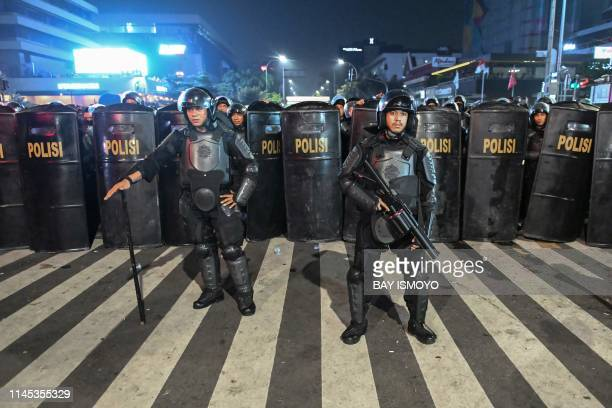 Indonesian police officers stand lined up before dispersing protesters during a demonstration outside the Elections Oversight Body in Jakarta on May...