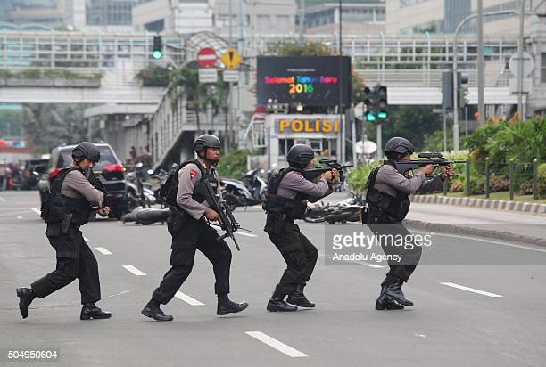 Indonesian police officers take security measures near the location of explosions after a series of blasts hit the Indonesia capital Jakarta on...