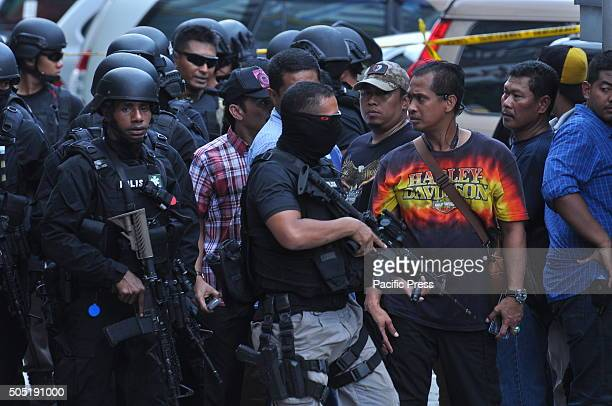 Indonesian police officers take security measures near the location of explosions after a series of blasts hit the Indonesia capital Jakarta