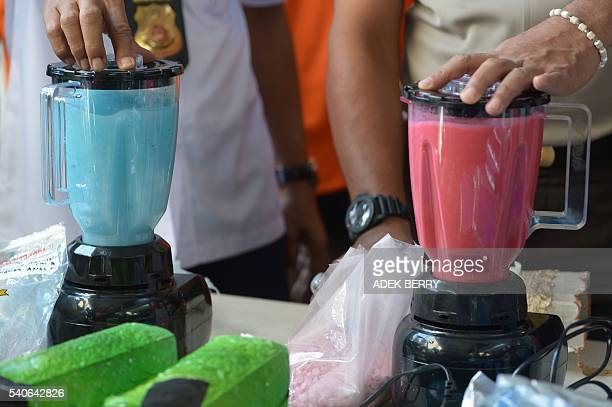 Indonesian police officers use blenders to destroy amphetamine tablets during a presentation to the media as part of the country's campaign against...