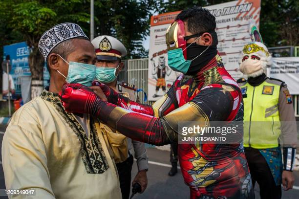 Indonesian police officers wearing Indonesian superhero costumes on the street adjusts a face mask in Pasuruan, East Java on April 9 amid concert to...