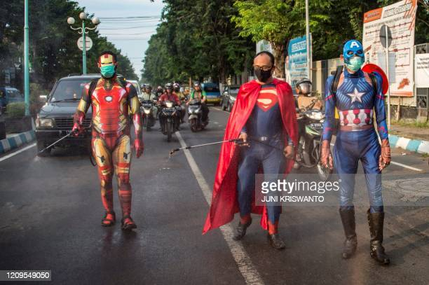 Indonesian police officers wearing superhero costumes on the street disinfect motorists' vehicles in Pasuruan, East Java on April 9 amid concert to...