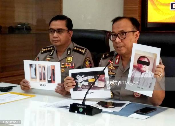 Indonesian police personnel show photographs of leader Para Wijayanto and various seized items at a press conference in Jakarta on July 1 as...