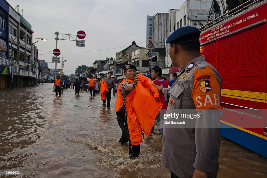 Indonesian police prepare as the Ciliwung River overflows in East Jakarta district on January 18, 2013 in Jakarta, Indonesia. According to the National Disaster Management Agency, about 50 percent of the capital is under water following the floods which have so far claimed eleven lives and displaced thousands of Indonesians.