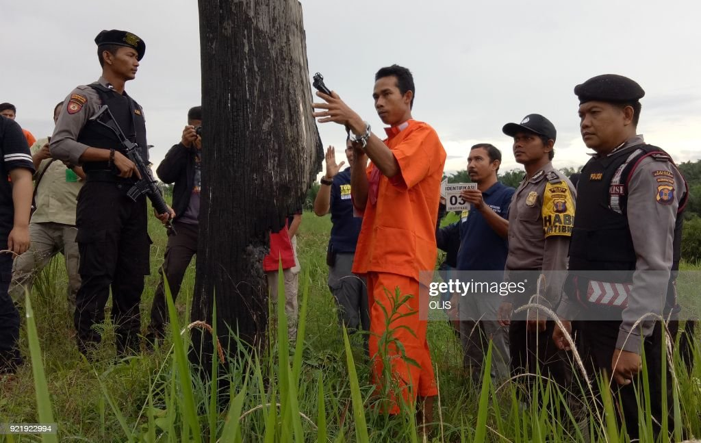 Indonesian police reconstruct the killing of an orangutan at the crime scene with the accused (in orange) in a field in Sangata, East Kalimantan on February 21, 2018. Four Indonesian men were arrested over the killing of an orangutan shot some 130 times with an air rifle, police said on February 19, in the latest fatal attack on a critically endangered species. /
