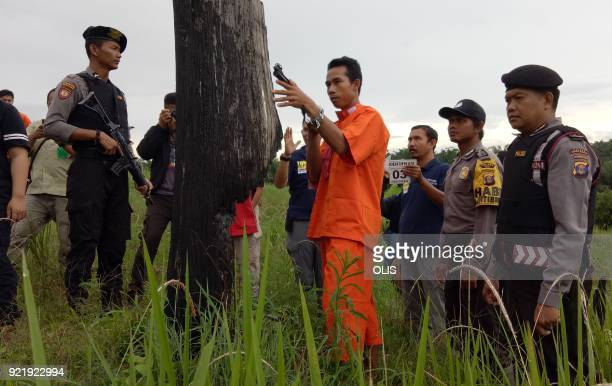Indonesian police reconstruct the killing of an orangutan at the crime scene with the accused in a field in Sangata East Kalimantan on February 21...