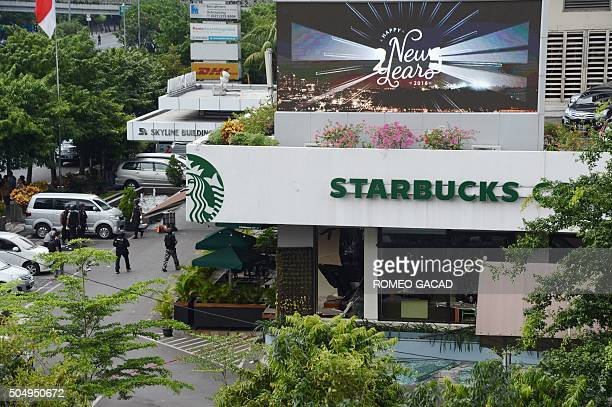 Indonesian police secure the area outside a damaged Starbucks coffee shop after a series of explosions hit central Jakarta on January 14 2016 Gunfire...
