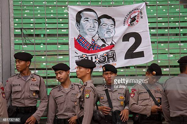 Indonesian police stand by to next to an election poster for Presidential candidate Joko Widodo on July 5 2014 in Jakarta Indonesia Today marks the...