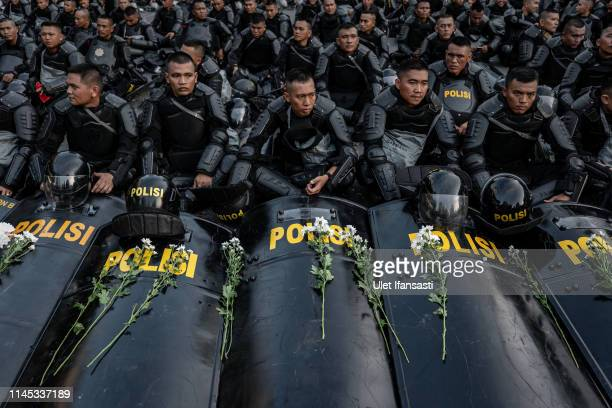 Indonesian police stand guard as they block protesters during a demonstration in front of the Elections Supervisory Agency after the official...