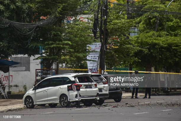 Indonesian police stand guard next to damaged vehicles after an explosion outside a church in Makassar on March 28, 2021.