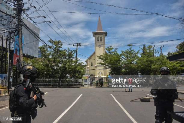 Indonesian police stand guard outside a church after an explosion in Makassar on March 28, 2021.