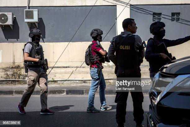 Indonesian police stand guard outside the Surabaya police station following another explosion on May 14 2018 in Surabaya Indonesia At least 10 people...