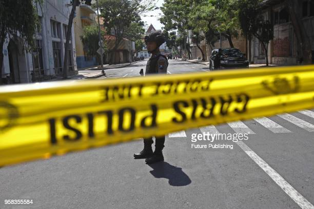 Indonesian police stand guard outside the Surabaya police station following another explosion on May 14, 2018 in Surabaya, Indonesia. At least 10...