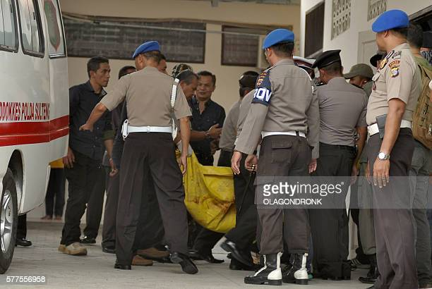 Indonesian police transfer a body bag from an ambulance at a local hospital in Palu Central Sulawesi province on July 19 after a firefight between...
