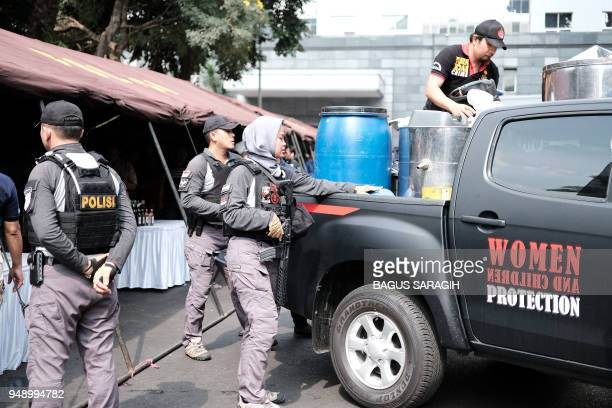 Indonesian police unload the stock of recently seized bootleg liquor prior to a press conference in Jakarta. - Police have arrested the main suspect...
