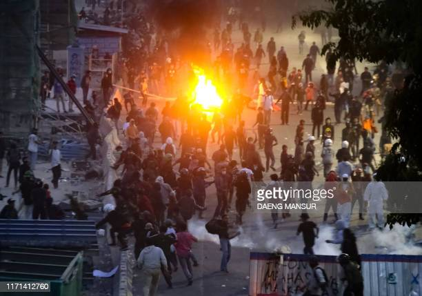 Indonesian police use tear gas to disperse student protesters rallying against divisive legal reforms, in front of a parliament building in Makassar,...