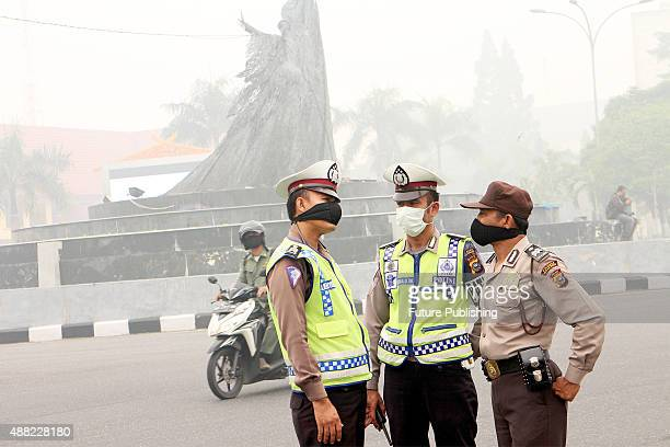 Indonesian police wear masks during stand guard demonstration against wild fires on September 14 2015 in Riau province Indonesia The thick haze has...
