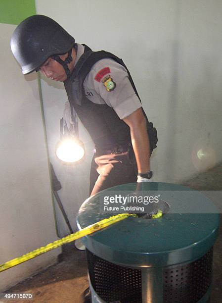 Indonesian policeman from an antiterror and bomb squad investigates blast site at the mall Alam Sutera on October 28 2015 in Tangerang Indonesia...